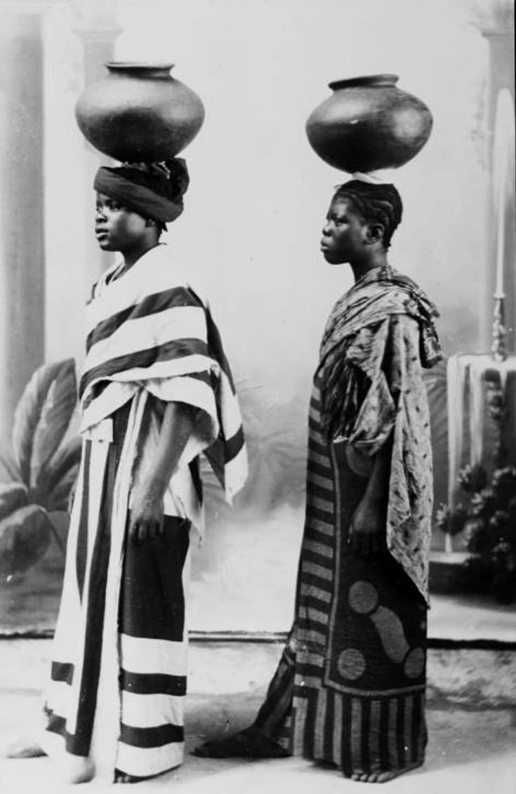 Two Swahili women posing in profile wearing flamboyant cotton robes, one wearing a turban, with both carrying water pots made of clay on their heads. Zanzibar. ca. 1900   print; A.C. Gomez.